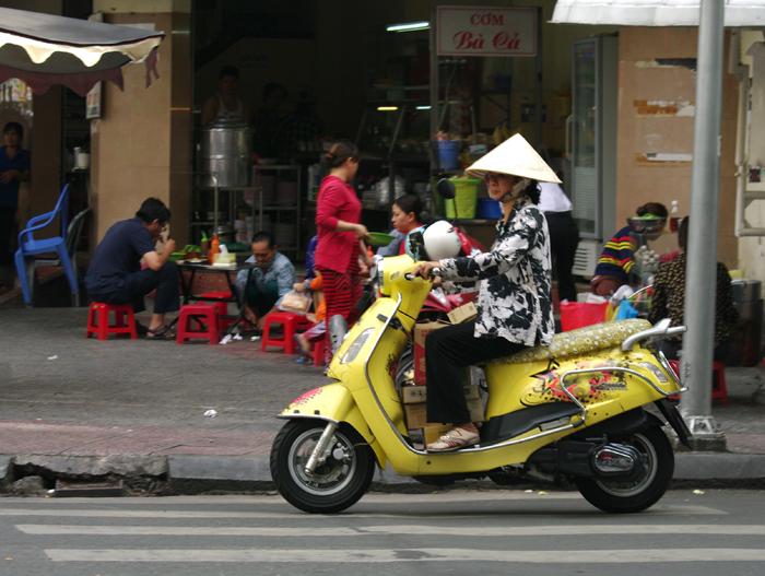 En las horas punta, impresiona ver los ríos, literalmente, de motos que entran y salen de las ciudades. Pero lo que más impresiona es que no existan horas valle. Los centros de las ciudades están abarrotados de motoristas que se mueven incansablemente de acá para allá a cualquier hora del día o de la noche.  Prohibiciones, las mínimas  Se supone que existen normas de circulación, pero el extranjero no las ve, a menos que los vietnamitas utilicen un código oculto, tipo jugador de mus. Las motos circulan como quieren, por aceras, por los mercadillos callejeros abarrotados de gente... y siempre parecen tener prioridad.   En la moto uno puede hacer la compra sin bajarse, hablar por el móvil, merendar... Está permitido que viajen un máximo de dos adultos en cualquier modelo y que lo hagan con todos los niños que quepan. Hay mamás que llevan a sus bebes colgados o entre las piernas, hay papás con tres niños en fila a su espalda agarrados unos a otros, hay niños que van en una trona de comer anclada sobre la moto, hay matrimonios que llevan a sus dos hijitos entre medias... Los motoristas deben llevar casco obligatoriamente, pero los niños no suelen usarlo.